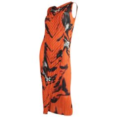 Striking dress from Issey Miyake's Fete line is made of orange fabric that is permanently pleated with an almost ghostly abstract print in black and white. Contrasting pleats in a chevron pattern run