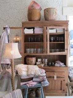 Rustic storage, pretty papier-mache bins, glassware, linen tablecloths and floral napkins