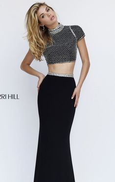 Make a wow statement in this two-piece set gown, Sherri Hill 32303. High neckline with beaded trim is perfectly styled with short sleeves. The crop top is styled with textured fabric and cut with a lovely opening at the back for a more noticeable appeal. Beads continue rounding the waist and segue to a full length slim skirt.