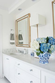 """Beautiful white bathroom features a a white dual washstand accented with polished nickel knobs and a white quartz countertop fitted with oval sinks paired with polished nickel faucets fixed in front of marble hex backsplash tiles positioned beneath Two Uttermost Palais Beaded 30"""" x 40"""" Gold Wall Mirrors illuminated by a French brass wall sconce."""