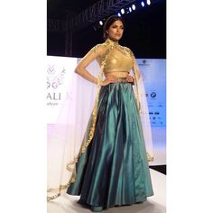 """Tall, mighty and prestige struck in @anjalikcouture's splendid regal teal lehanga with a jewel gold blouse and a royalty sheer embroidered cape embellished with turquoise stones adding to the festive couture silhouette from our """"Modish Renaissance"""" Summer Resort 2015 Collection  #Embroidered #Embellished #Cape #Sheer #Bridal #Royalty #Teal #Lehanga #Gold #AnjaliKCouture #ModishRenaissance #StudioRudraksh #PuneFashionWeek #Dubai #Saudi #Pune #India"""