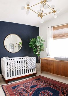 modern brass bubble chandelier with dark navy walls, white crib, gold over-sized mirror, mid-century modern credenza, fiddled fig tree in a bast and boho rug