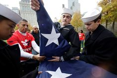 America honors its veterans - New York - Sea Cadets Daniel Cheng, left, Thomas Kessler, center, and Jack Toll help veterans advocacy group Team Red White and Blue fold a large American flag at the National September 11 Memorial on Sunday, Nov. 9, 2014, in New York. The 9/11 Memorial and Museum honored veterans throughout the weekend, leading up to Veterans Day, Nov. 11. The cadets are members of the John T. Dempster, Jr. Division in Trenton, N.J.
