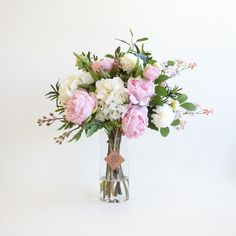 Lovely fluffy pale pink artificial peonies and white hydrangea are the star of this arrangement, with lovely pom pom dahlias and gorgeous life like viburnum flowers and eucalyptus berries with mixed garden foliage.