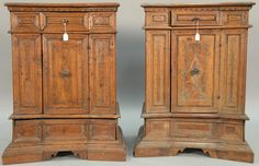 Pair of walnut side cabinets having shaped tops over conforming cabinets with one small drawer over one door over bottom pull out base to reveal covered drawer, German or North Italian. Realized Price $3,000.00