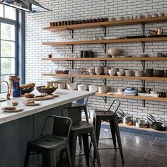 Open shelves and white metro tiles create an industrial feel in this modern kitchen.