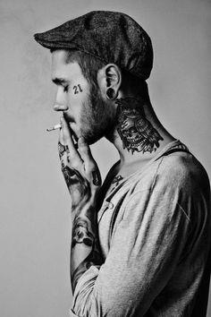 Henley. Cap. Tattoos. Cigarette.