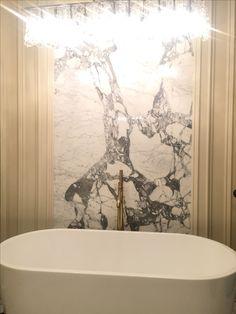 Statuario marble slab back splash wall, ligne crystal chandelier, freestanding modern oval bathtub, heavy brass tub faucet, and custom paneling. Statuario custom tile 18x9 patterned.