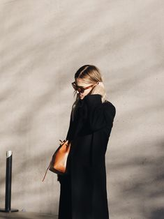 Black cashmere coat, Acne Studios sunglasses & knit jumper, Mansur Gavriel bag. Via Mija