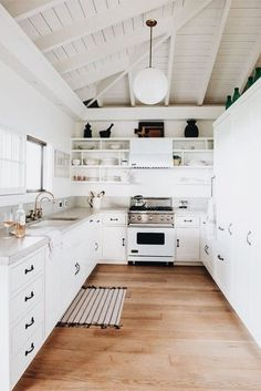 Gorgeous all white kitchen with wood floors and open shelves on both side of the oven. ☼ ☾
