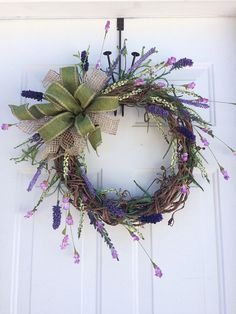 Airy, natural and beautiful come together with this Spring wreath! Built on a 14 grapevine wreath, it measures 25x20. Artificial lavender, cream & purple heather and green baby ferns adorn this wreath creating a half moon spray. The bow is created with two different ribbons: a