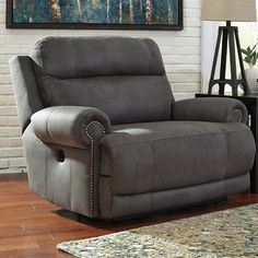 """While minimizing space requirements and sparing that """"puffy"""" look you might expect from a recliner, this zero wall recliner doesn't hold back when it comes to contemporary style. Subtle touches such as sporty jumbo stitching, nailhead trim and a """"weather worn"""" effect on the upholstery give this handsome piece a buttoned-up appeal and fresh feel."""