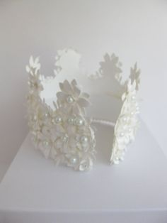 This is a one of a kind, handmade paper crown. Each paper flower is embellished witha glass pearl in the center. The crown is flexible and can be