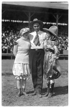 This photo shows Ed McArty standing in a rodeo arena, with his arms around two girls: Donna Card on the left and Ruth Roach on the right.