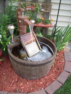 Barrel water fountain. Added old glass washboard with a color changing led solar light behind it. Looks awesome at night! Also added walkway solar lights to sides of pump to add some small light to fountain.