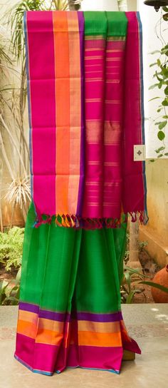 BOTTLE GREEN kanchivaram kora silk WITH A CONTRASTING MULTI colour BORDER in PURPLE, pink, GOLD and ORANGE. The BRIGHT PINK pallu is interlaced with some golden zari lines that enhances the sari.