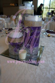 Atop a #square #mirror, this #elegant #candle #set #centerpiece has #three #purple #irises #submerged in each #vase. The #mirror and #gold #rhinestone #buckles on #vases help increase #radiance.