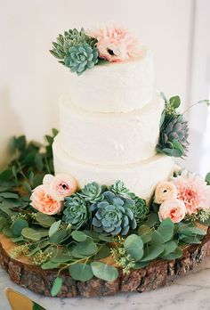 A three-tiered white wedding cake decorated with greenery, succulents, peonies, ranunculus, and dahlias | Brides.com