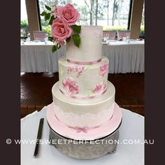 Hand-painted floral wedding cake with custom sugar flowers and lacework.