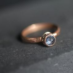 This ring is a handmade and handset. Custom alloyed color of 14 karat rose gold.  A 2mm half round band size featuring 4-4.5mm mm natural blue violet high dome rose cut sapphire. Surround by 19 bread set 2 mm Cream White diamonds. Pale blue sapphire, ethical sapphire, ethical jewelry, rustically wedding