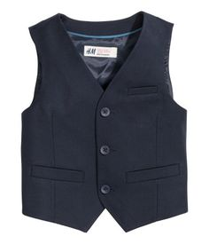Suit vest in woven fabric. Buttons and mock pockets at front and decorative tab at back. Lined.