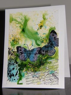 I've been having a lot of fun learning to use brusho.  One thing I have learned is that coated card stock is the easiest to work with.  I'm lucky to have a paper distributors close by and can get off cuts relatively cheaply :). I stamped the butterflies and put a liquid mask over them and let it dry. I then stamped the rest of the card.  I sprinkled green brusho over the coated card stock and spritzed with water.  I forgot the ranger pen's would also run a little, but with the brusho colour…