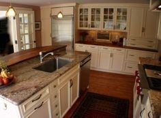 grayish granite, dark floors and white cabinets