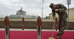 US Army personnel cleans the red carpet ahead an inauguration ceremony of the US anti-missile station Aegis Ashore Romania (in the background) at the military base in Deveselu, Romania on May 12, 2016