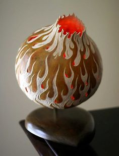 Flamethrower by A.V. Browning Carved long neck gourd lamp with flame pattern and teardrop shaped hardwood base.