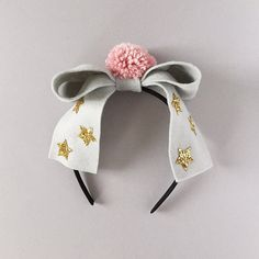 Oversized Grey Felt Bow with Carnation Pink Pompom Center, and gold glitter stars. Attached to a hard satin headband that fits aprox. ages 1 year old to adult. *** PLEASE READ SHOP/SHIPPING POLICIES BEFORE PURCHASING*** *** Some pieces may contain small parts. Do not leave children unattended while wearing accessories from Giddy Up and Grow. Customer acknowledges full responsibility.*** Handmade with great care and detail since 2010 ©2010-16 Giddy Up & Grow