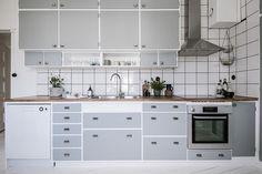 Stängda skåp med tidstypiska beslag varvas med öppna hyllplan i en tilltalande estetik.. Birger Jarlsgatan 24E - Bjurfors