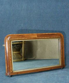 Beautiful antique mahogany cross banded over mantle mirror, attractive inlayed frame with inner gilt wood moulding.  Excellent condition for age, some very slight degradation to the reflective surface only evident on very close inspection.  Measures 75 cm X 45 cm.