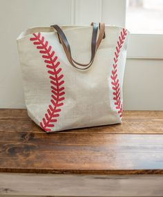 """Our baseball tote bag is approximately 22""""W x 8""""D x 17""""H. Fully lined with zippered pocket inside. Due to the popularity of this item, its current ship time is 10-15 business days."""