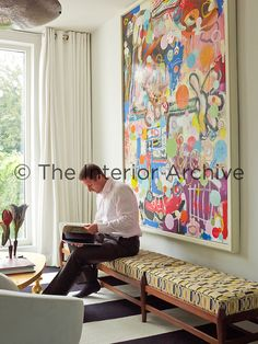 The owner of the house is seated next to a large abstract painting which takes up an entire wall of the light and airy living room