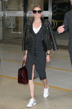 Olivia Palermo wears striped midi dress with white tee, sneakers and black studded leather jacket.