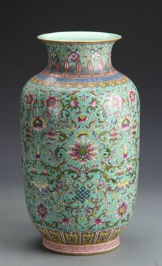 China, ROC Period, Famille Rose vase, with a bright turquoise ground color, decorated with a dense pattern of scrolling lotus flowers and auspicious symbols. Qianlong mark on base. Height 13 in., Width 7 in.