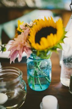 sunflower centerpiece idea http://www.weddingchicks.com/2013/09/25/colorful-backyard-wedding/
