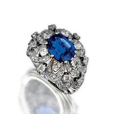 SAPPHIRE AND DIAMOND RING, CIRCA 1940.  The domed mounting of floral design, set with an oval sapphire surrounded by open work petals of circular-and single-cut diamonds, mounted in white gold