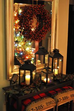 Wreath on a Mirror above a Foyer Table. I love that the Christmas Tree lights are reflected in the mirror.