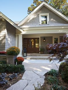 Cedar shake siding with very wide and decorative window trim and a wood-looking door.
