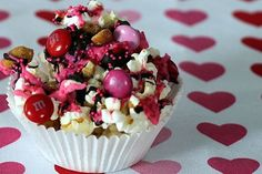 Pretty in Pink Popcorn served in a cupcake liner.  This would be cute for Valentine's Day wrapped in cellophane as a party favor.  Plus lots of other fun popcorn recipes and ideas.