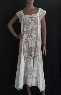 Mixed lace tea dress, late 1920s. The cut is straight to the hipline, below which the layered skirt is bias cut and flared on the sides. The crisp, pristine cotton dress has wide center panels of filet lace roses