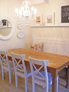 Dining table against a wall with a pew