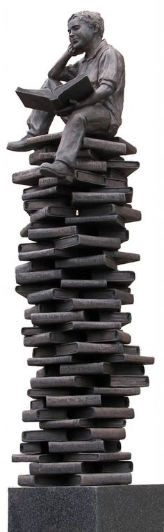 statue/sculpture of boy reading perched on a stack of 100 books, celebrating centennial of the Coshocton Public Library in Ohio, USA