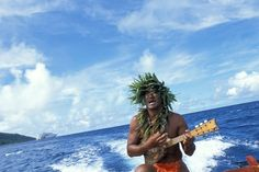 she could hear Mr. Rene coming as he sang a Tahitian song while strumming his little guitar.  Palm fronds and beautiful pink flowers wrapped around the poles holding the up the shade tarp.  He serenaded her as he pulled up to the dock.