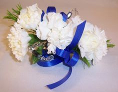 White carnation wrist corsage with blue ribbon and black and clear crystals. Wrist corsage by Seasonal Celebrations. http://www.seasonalcelebrations.com