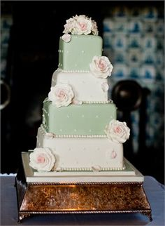 A vintage style cake with large open cream roses dusted with pale pink.  Alternating tiers of cream and sage green make this a stunning and classic wedding cake.