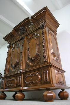 Richly decorated two-door wardrobe. Two drawers at the bottom. The door panels are framed with pilasters topped with carved capitals. A top of a repeatedly cut and broken moulding, decorated with carved coat of arms with a motif of an eagle against a background of acanthus leaves. Dimensions:  H 2.4 m; W 1.8 m; D 0.7 m.  Material - European walnut on a pine frame.