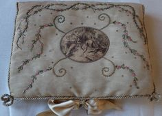 This is a pretty silk padded handkerchief folder, dating from the early 20th century. It measures 9 ins x 12 ins, depth around 1.8 ins. Pale coffee coloured silk with gold sequins and pink and green silk ribbon embroidery.   eBay!