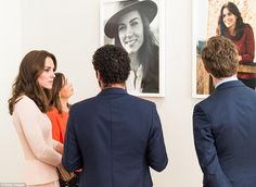 Kate Middleton stands next to the cover image for her Vogue debut, which shows her wearing a brown suede trench and vintage trilby